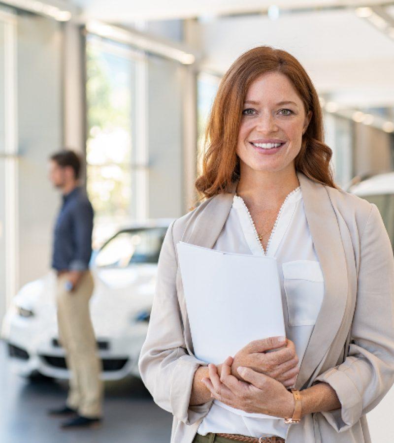 satisfied-saleswoman-in-car-dealership-DUKB7JX.jpg